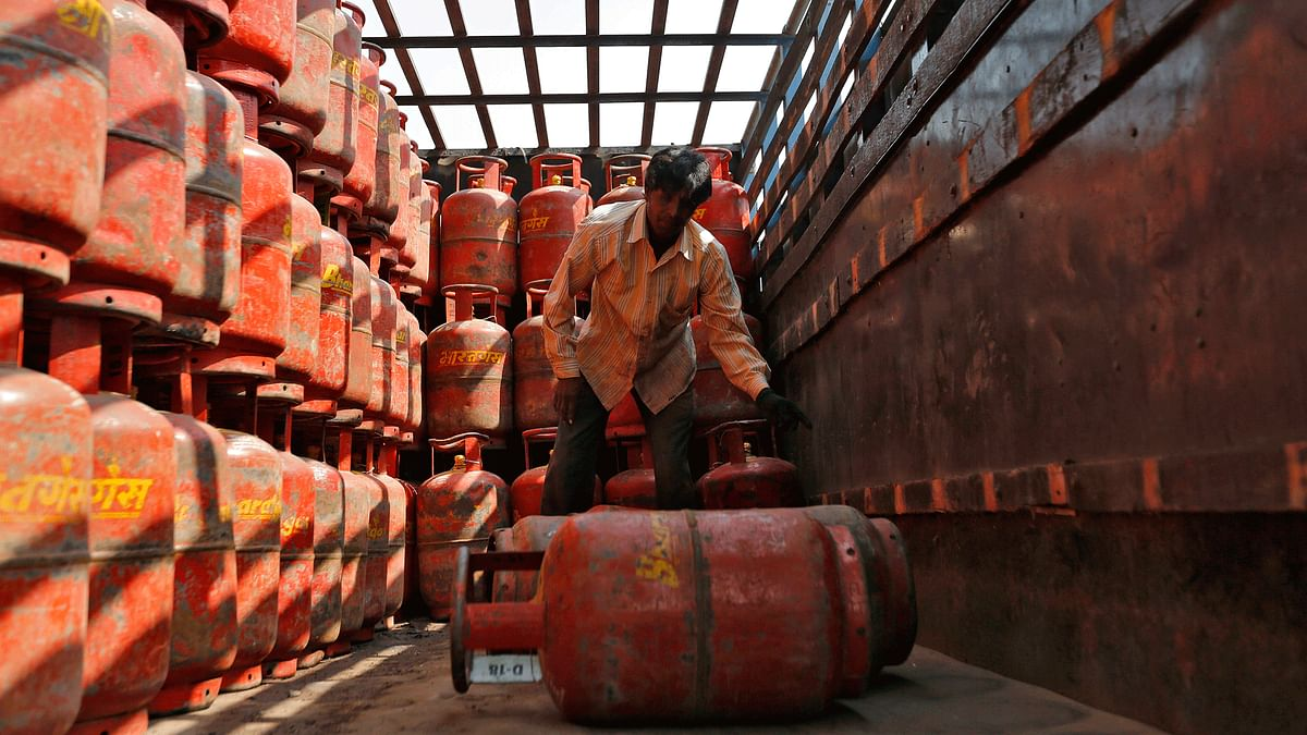 A worker unloads liquefied petroleum gas (LPG) cooking cylinders from a supply truck outside a distribution centre. (Photo: Reuters)