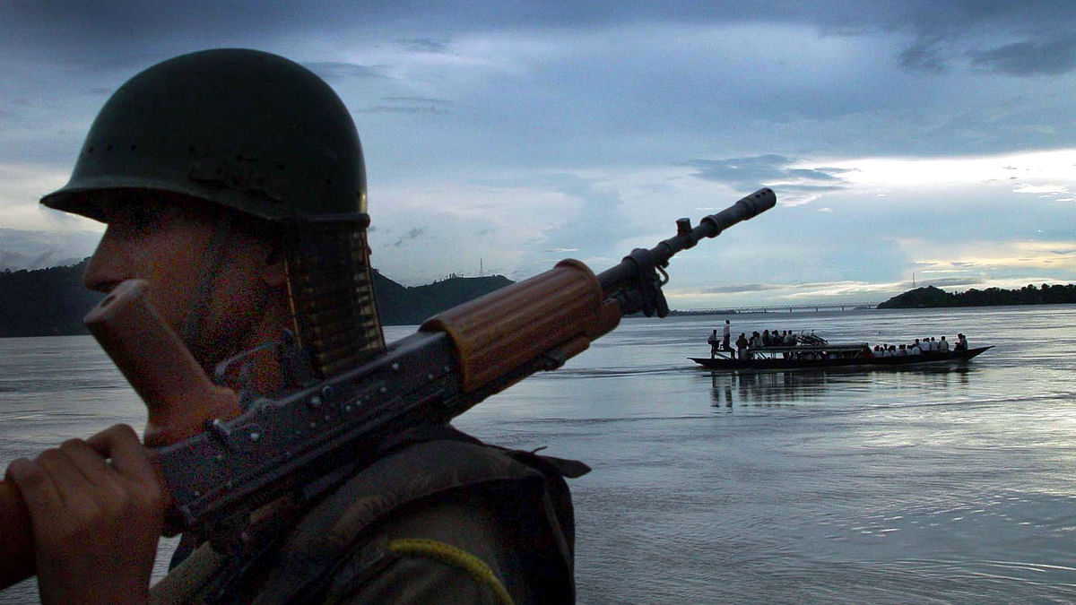 An Indian paramilitary trooper stands guard on the banks of  Brahmaputra river on the outskirts of Guwahati, 12 August 2002. (Photo: Reuters)
