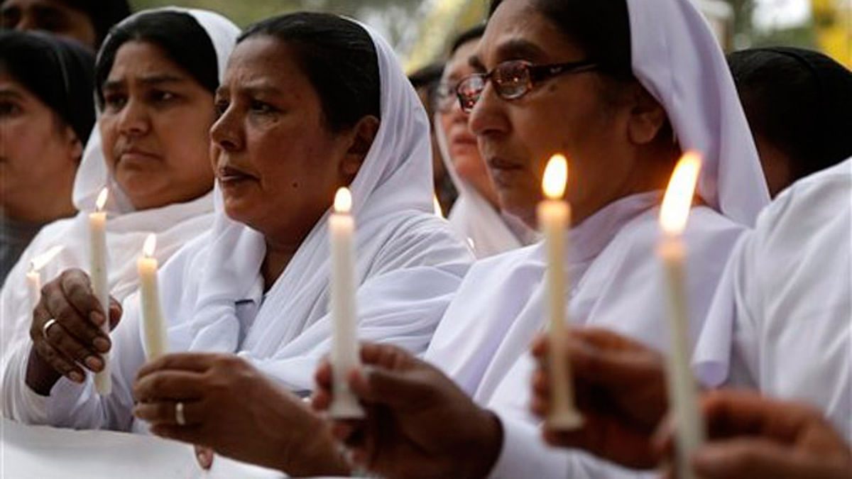 Pakistani nuns hold candles during a vigil for victims of Sunday's deadly suicide bombing in a park. (Photo: AP/KM Chaudary)