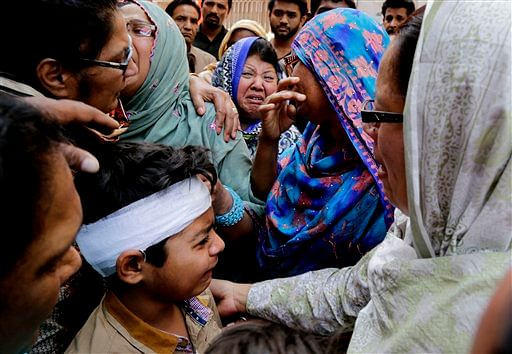 Eric John, bottom, who survived Sunday's attack, cries during the funeral of his cousin, in Lahore. (Photo: AP/KM Chaudary)