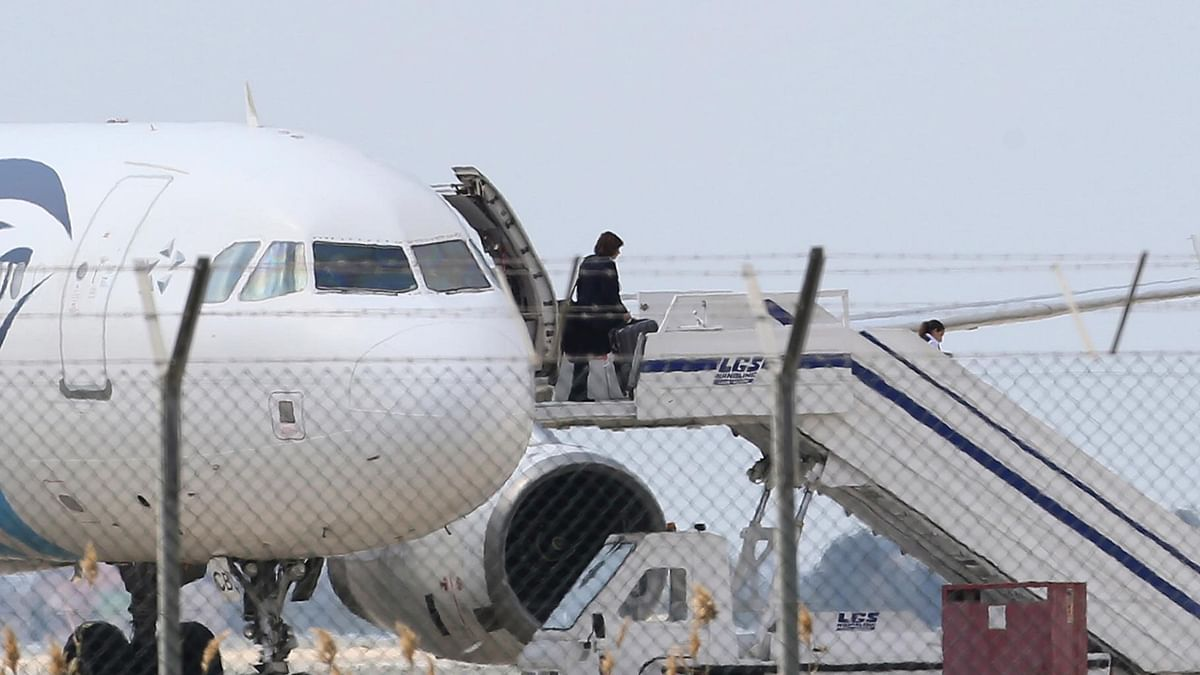 A passenger leaves the hijacked EgyptAir aircraft after landing at Larnaca Airport in Cyprus. (Photo: AP)