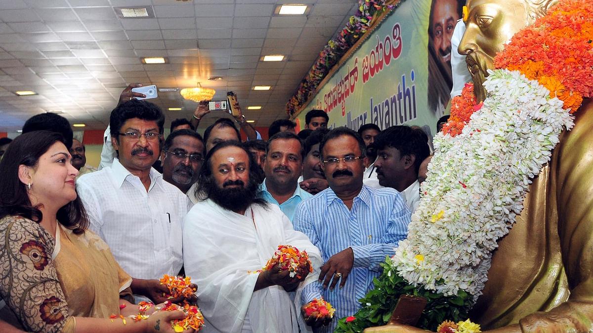 The Art of Living founder Sri Sri Ravi Shankar pays floral tribute to Tiruvallur statue on the occasion of Tiruvallur Jayanti celebrations, in Bengaluru, on January 16, 2016. (Photo: IANS)