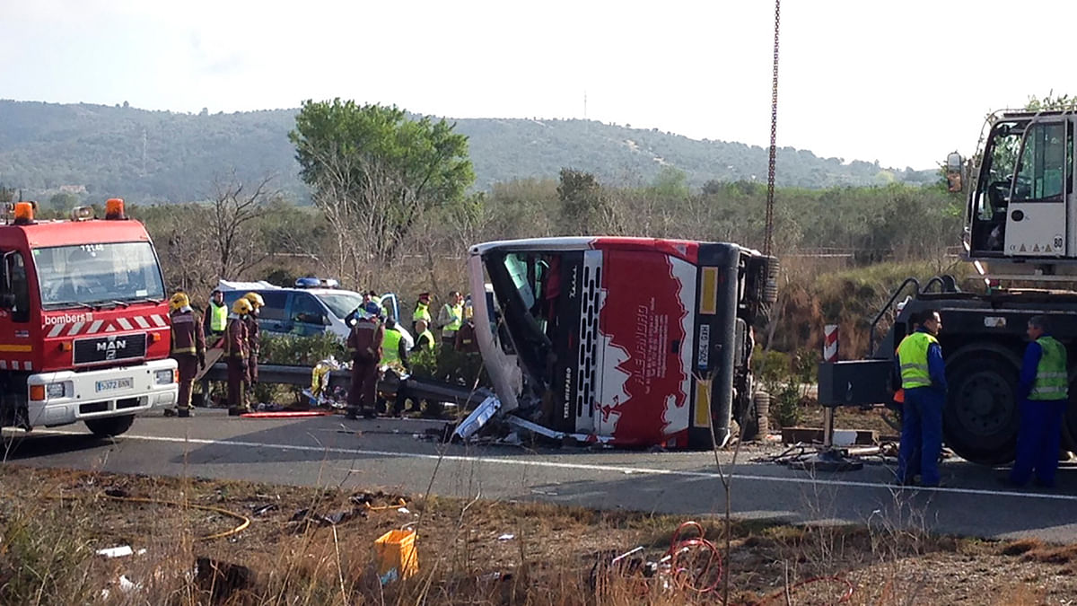 Emergency services personnel stand at the scene of a bus accident crashed on the AP7 highway that links Spain with France. (Photo: AP)