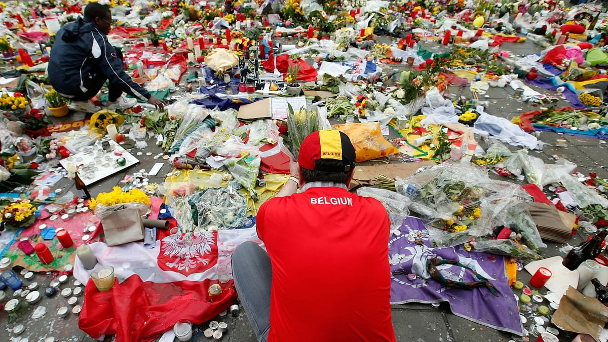Two men help re-adjust the tributes left for the victims of the recent bomb attacks in Brussels, following heavy rain in the Place de la Bourse in Brussels,  March, 28, 2016. (Photo: AP)