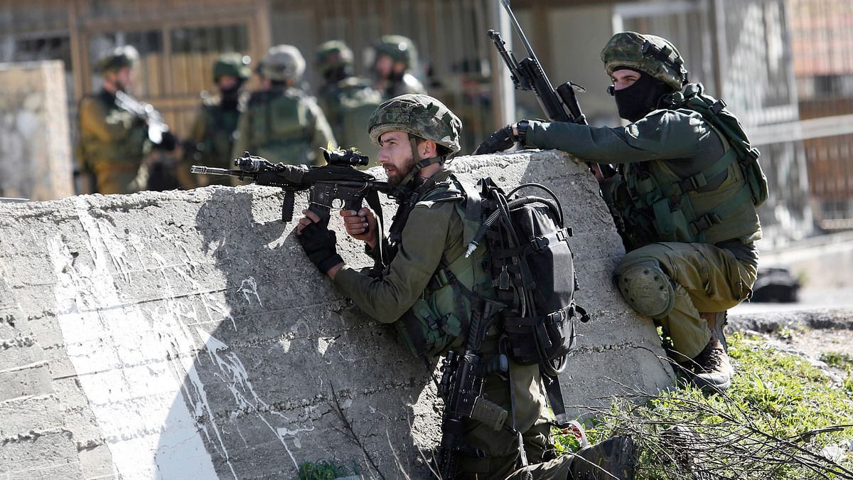 Israeli soldiers take positions during a raid to arrest a Palestinian at the Amari Palestinian refugee camp, near the West Bank