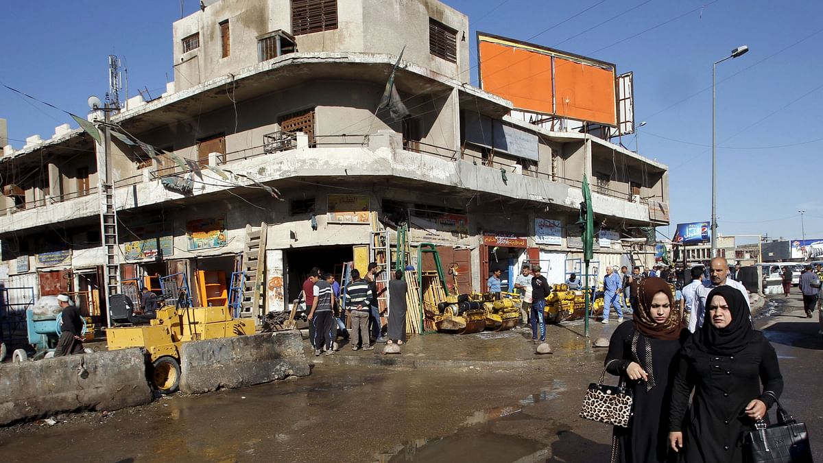 People walk past the site of a blast in Baghdad's Bab Sharji district. (Photo:Reuters)
