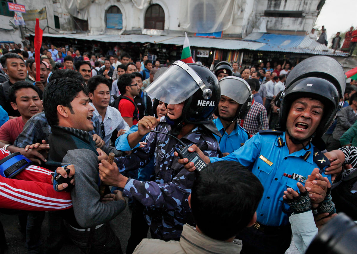 Nepalese protesters clash with policemen after burning a copy of the new constitution during the protest organized by splinter of the Maoist party, alliance of ethnic group and Madhesi party, in Kathmandu, Nepal, September 2015. (Photo: AP/Niranjan Shrestha)