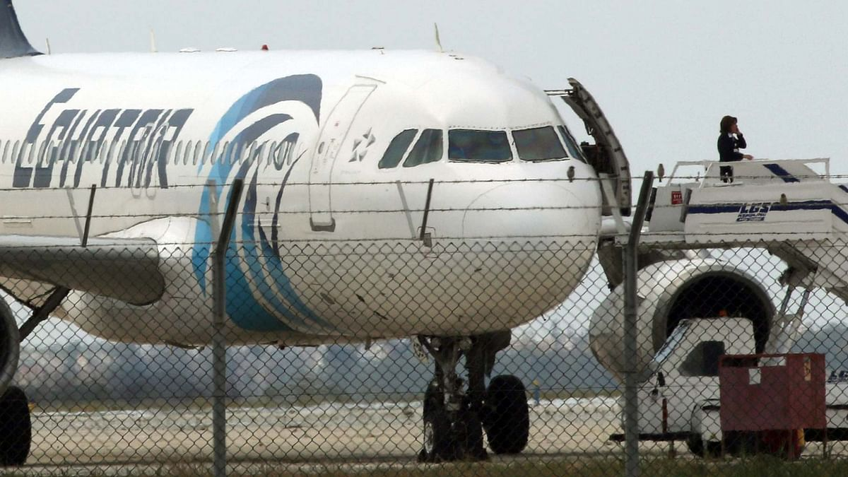 An official makes a call from the ramp of a hijacked Egyptair A320 Airbus at Larnaca Airport, Cyprus. (Photo: Reuters)
