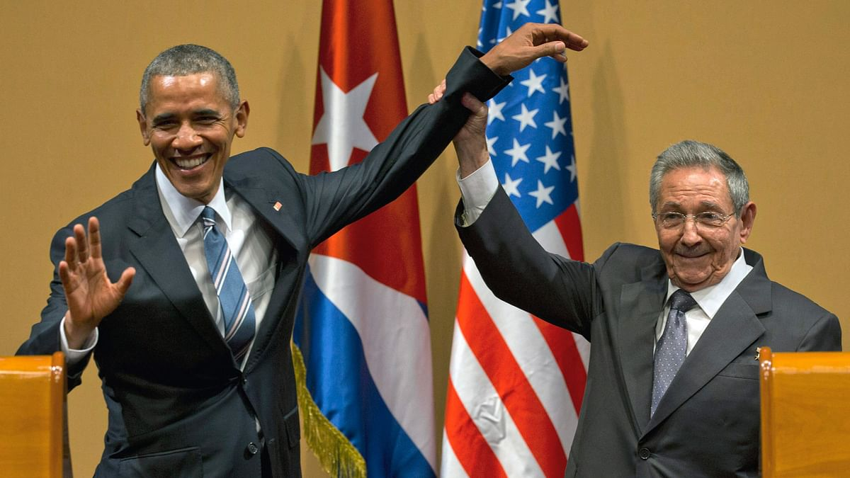 Cuban President Raul Castro, right, lifts up the arm of President Barack Obama at the conclusion of their joint news conference at the Palace of the Revolution. (Photo: AP)