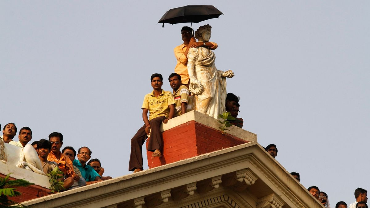 People stand atop  Writers' Building  to get a glimpse of  TMC chief Mamata Banerjee after she took  oath as the  chief minister,  in Kolkata May 20, 2011. (Photo: Reuters)