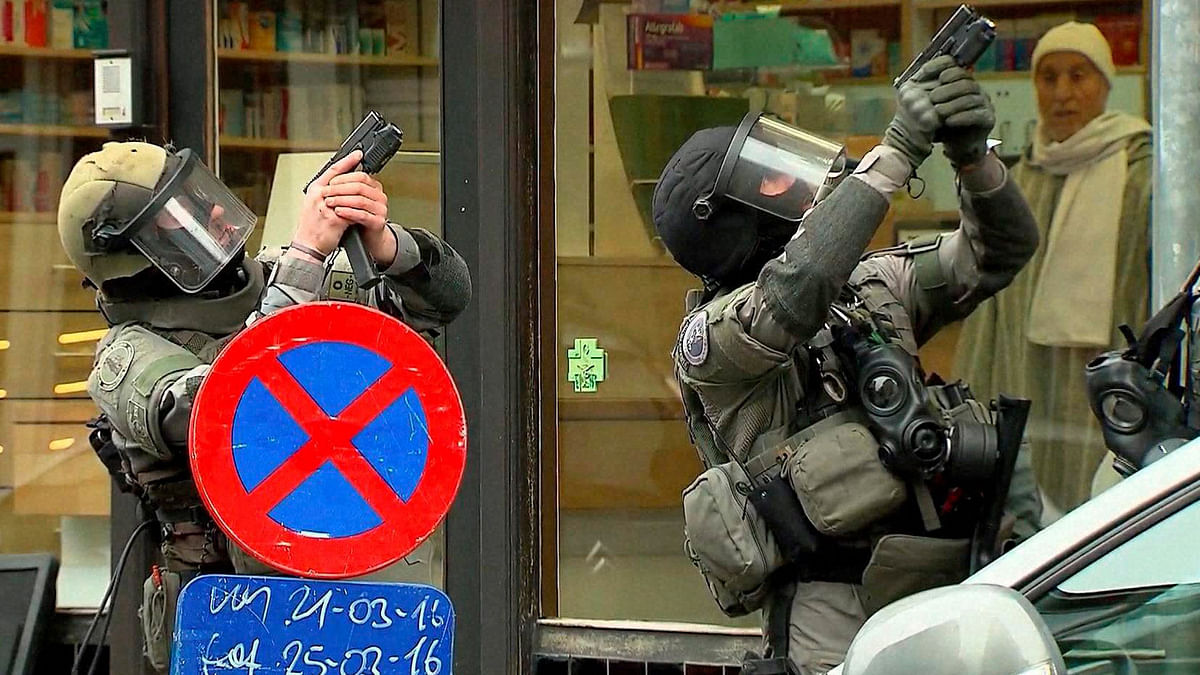 In this framegrab taken from VTM, armed police officers take part in a raid in the Molenbeek neighborhood of Brussels, Belgium, Friday March 18, 2016.