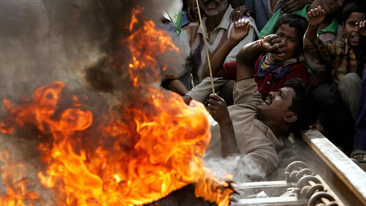 People lie near a fire they set on a railway track during a protest against the violence in Nandigram, in  Siliguri, West Bengal, 16 March  2007. (Photo: Reuters)