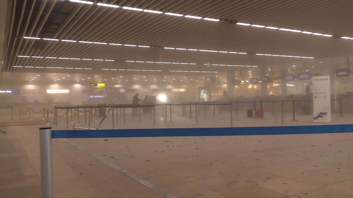 Travellers stand in a smoke-filled terminal at Brussels Airport, in Brussels after the explosions. (Photo: AP)