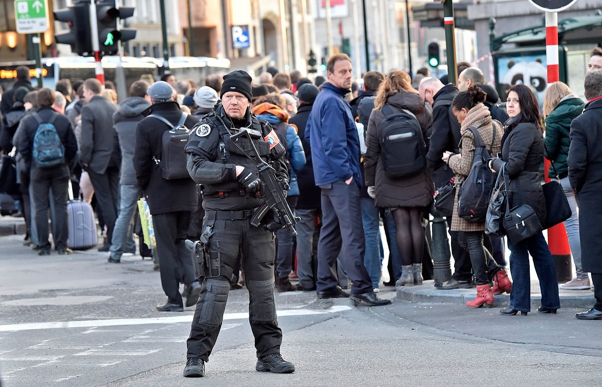 People queue for buses behind a policeman in Brussels, Tuesday, March 22, 2016.