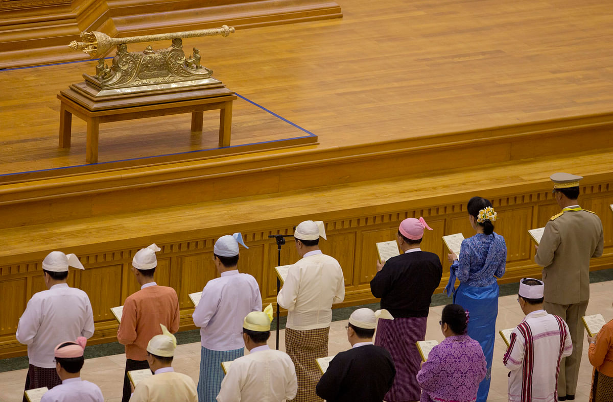 National League for Democracy party leader Aung San Suu Kyi, in blue, second right, takes oaths with other lawmakers as a cabinet minister at parliament. (Photo: AP)