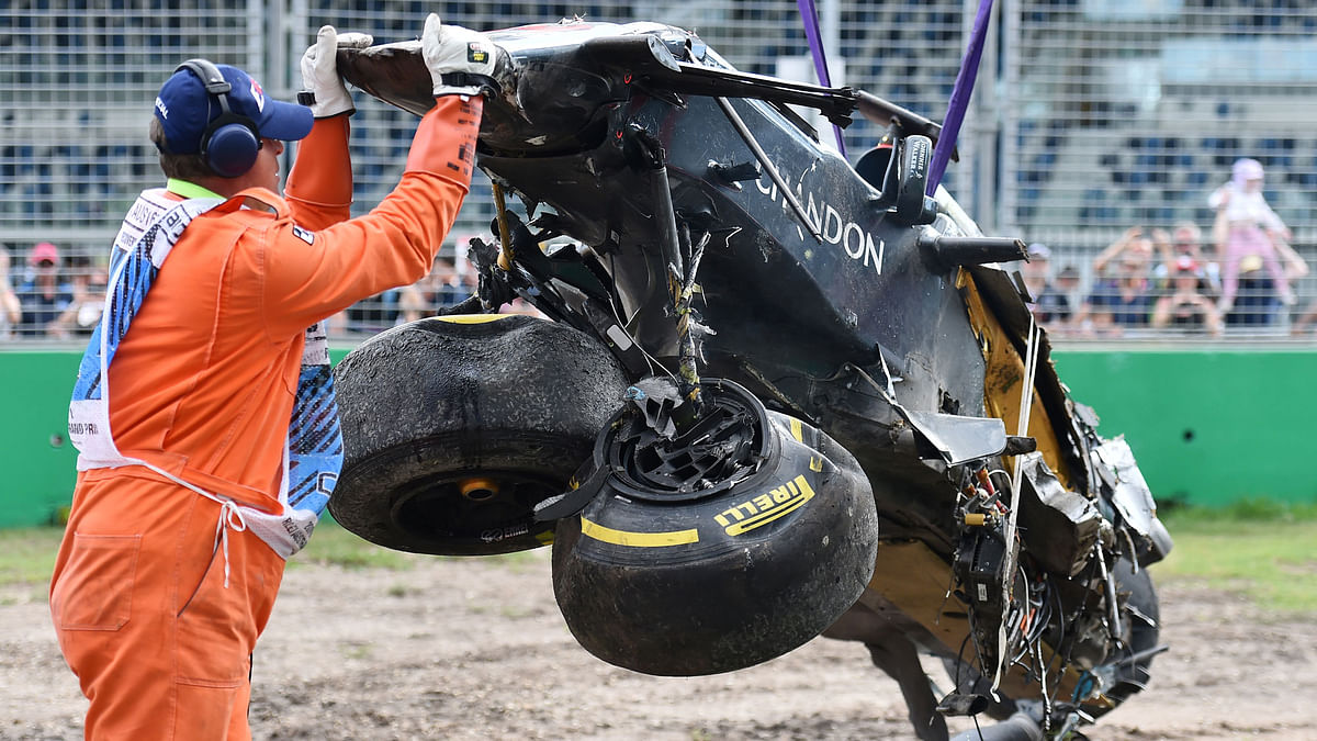 A track official assists the removal of McLaren driver Fernando Alonso's car. (Photo: AP)