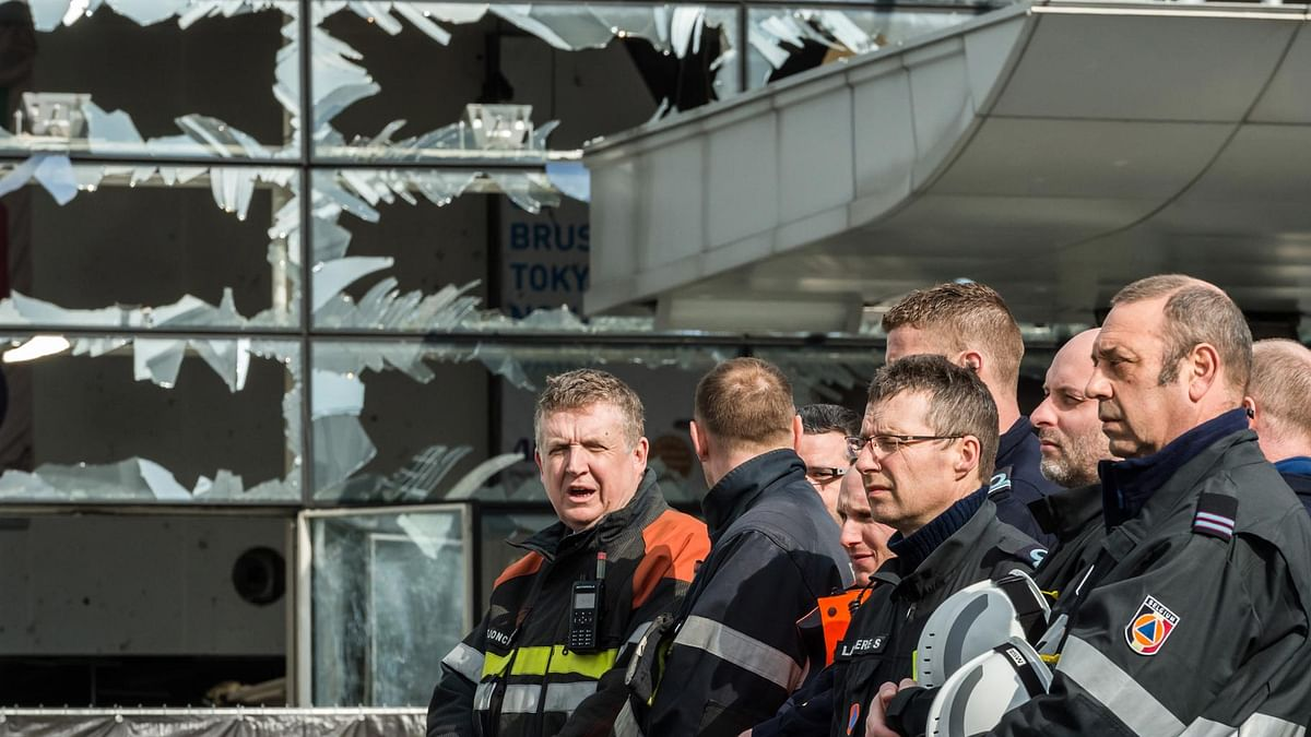 Firefighters and first responders stand next to blown out windows at Zaventem Airport in Brussels. (Photo: AP)