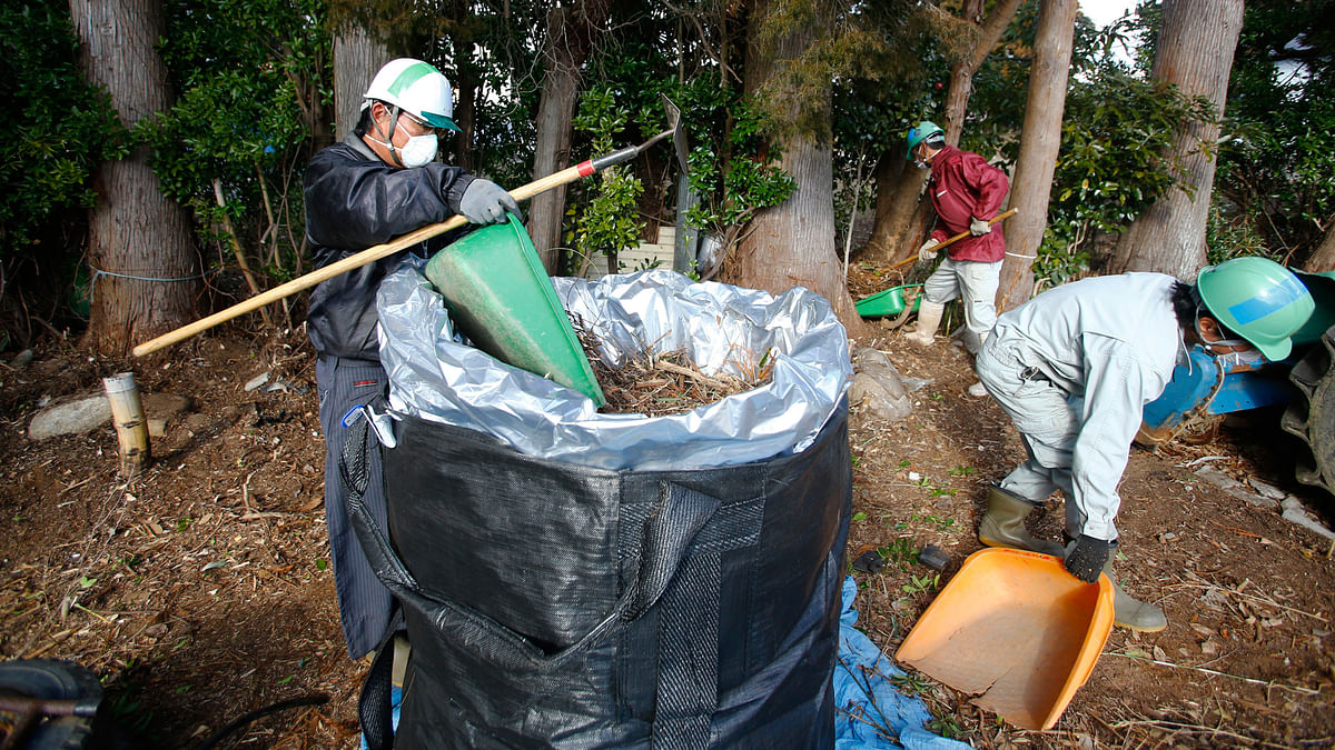 Workers clean radioactive soil and plants in a private home in Minamisoma, Fukushima Prefecture. (Photo: AP)
