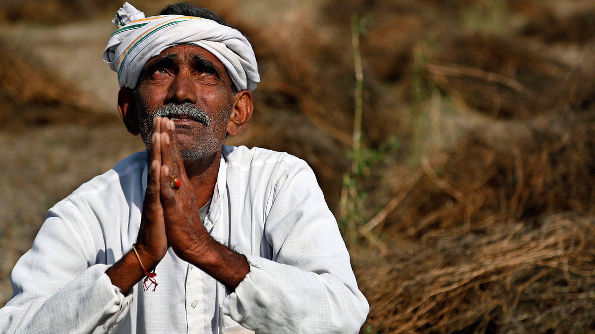 Farmer in a Rajasthan village looks skyward as he sits in his field with wheat crop that was damaged in unseasonal rains and hailstorm. (Photo: AP)