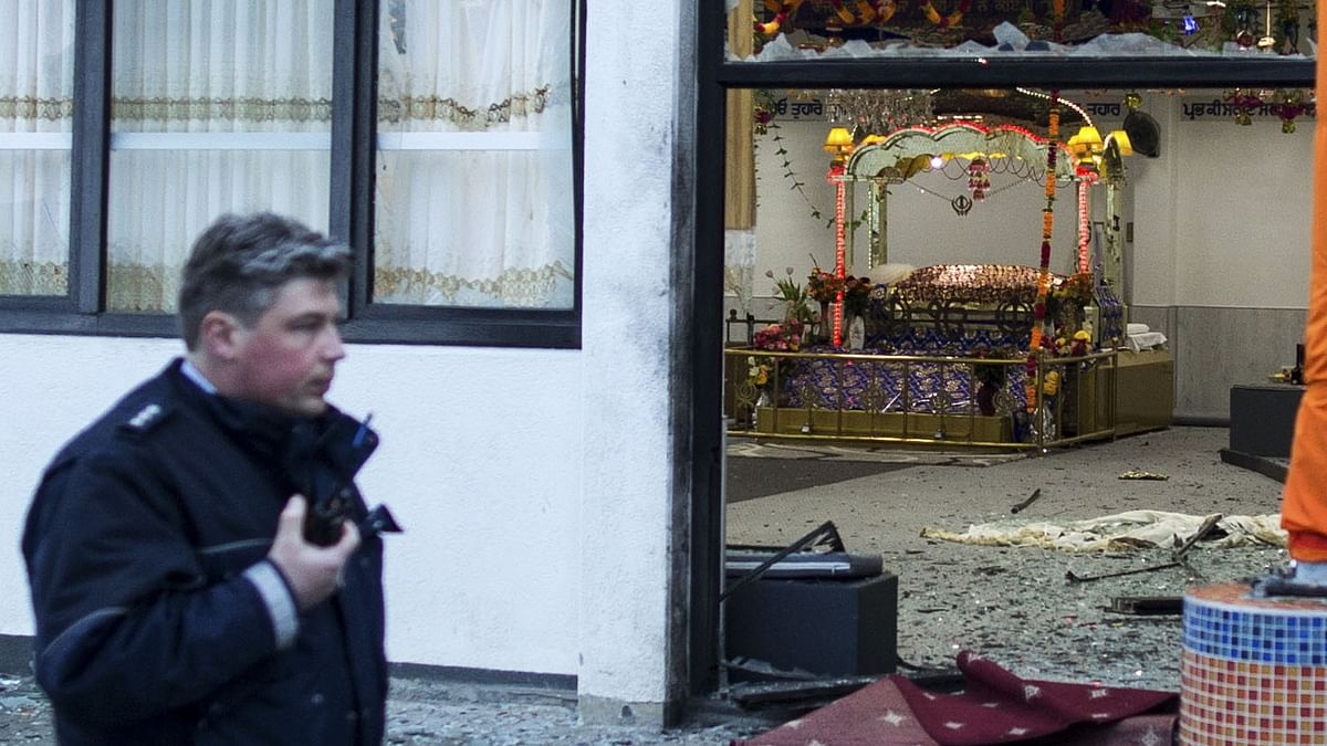 A police officer passes by the Sikh temple after three people were injured in the explosion, in Essen (Photo: AP)