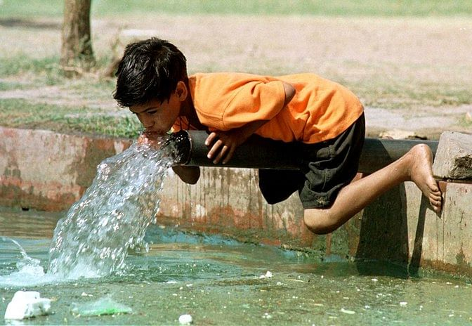 Child drinks water from roadside pipe in New Delhi during the summer heat. (Photo: Reuters)