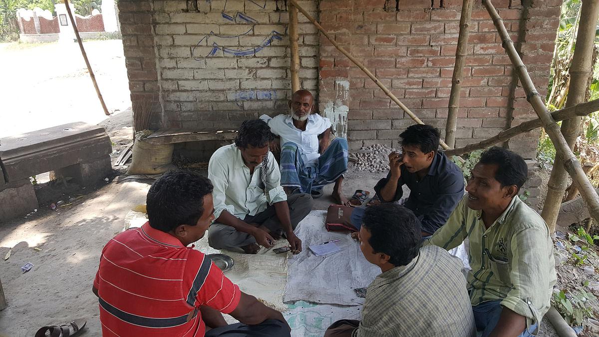 Karim Sheikh watching his friends play a card game, in Plassey, Nadia. (Photo: Chandan Nandy/ <b>The Quint</b>)