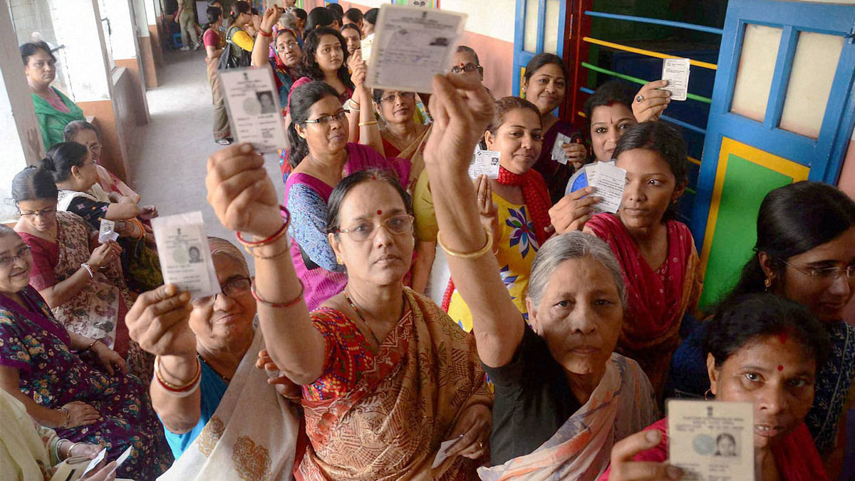 Women showing their voter cards during the 1st phase of West Bengal Assembly Elections in West Medinipur