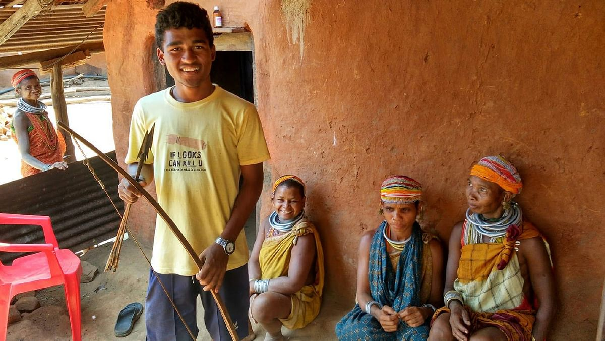 Arjun Kirsangi shows his indigenously made bow and arrow, as his aunts look over. He belongs to the Upper Bonda tribe of Malkangiri, and is the first person from his village to give his matriculation exams. (Photo: Ankush Vengurlekar)
