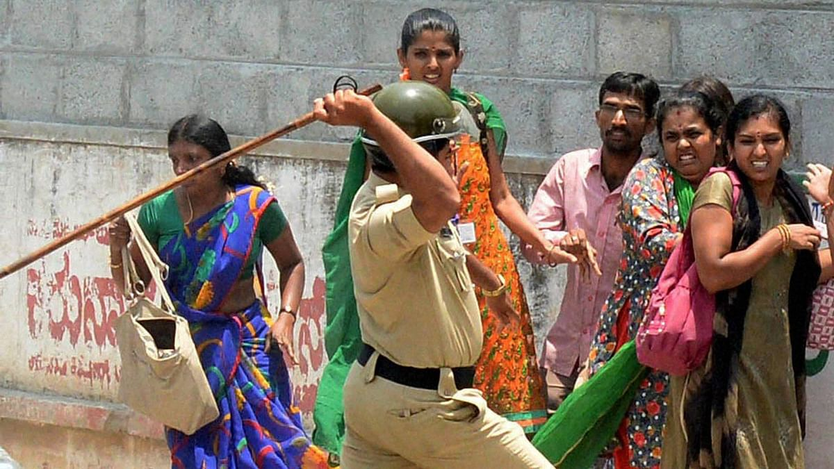 Police charge the garment factory workers who were protesting over EPF withdrawal norm, in Bengaluru on Tuesday.(Photo: PTI)