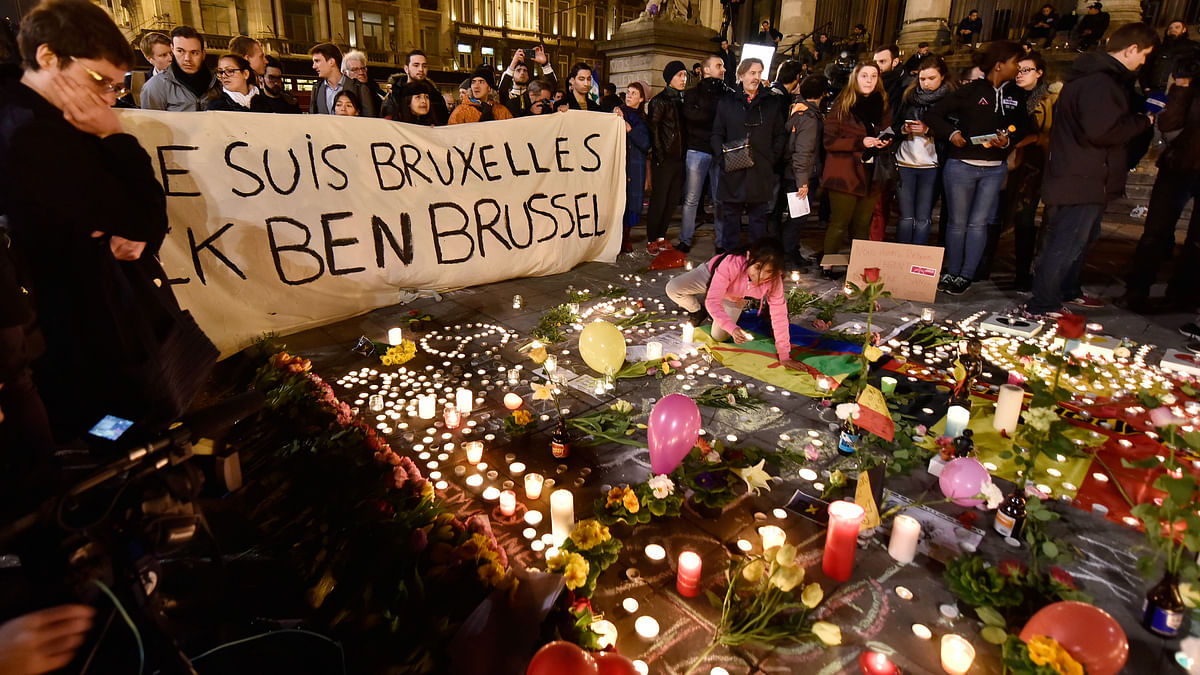 "People holding a banner reading ""I am Brussels"" behind flowers and candles to mourn for the victims at Place de la Bourse in the centre of Brussels, 22 March, 2016. (Photo: AP)"