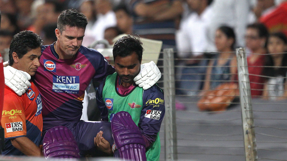 Kevin Pietersen being helped out of the ground after he incurred an injury. (Photo: BCCI)