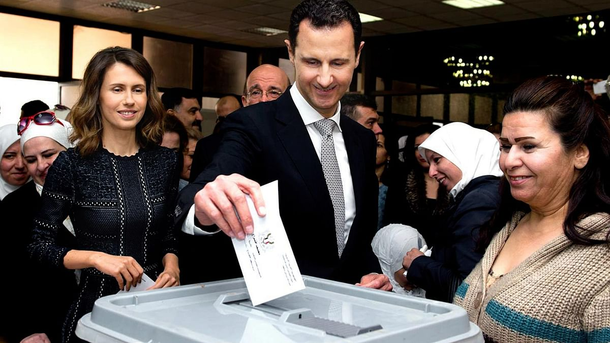 Syrian President Bashar Assad casting his ballot in the parliamentary elections, as his wife Asma, left, stands next to him, in Damascus, Syria, Wednesday, April 13, 2016. (Photo: AP)