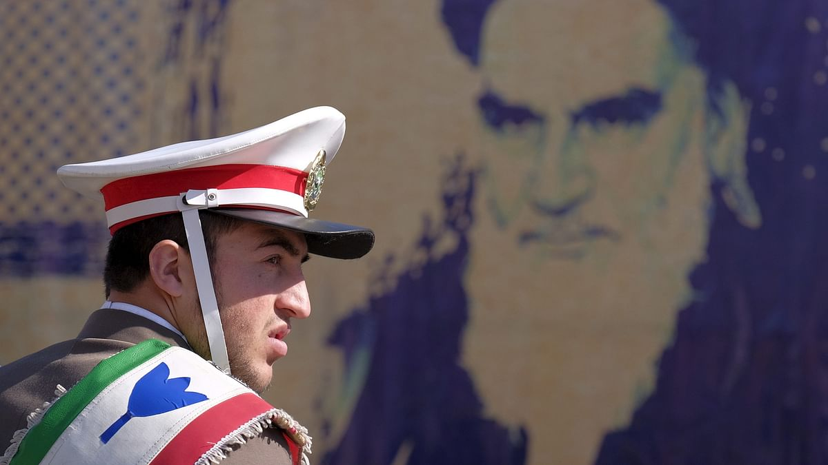 An Iranian soldier stands guard in front of a picture of Iran's late leader Ayatollah Ruhollah Khomeini. (Photo: Reuters)