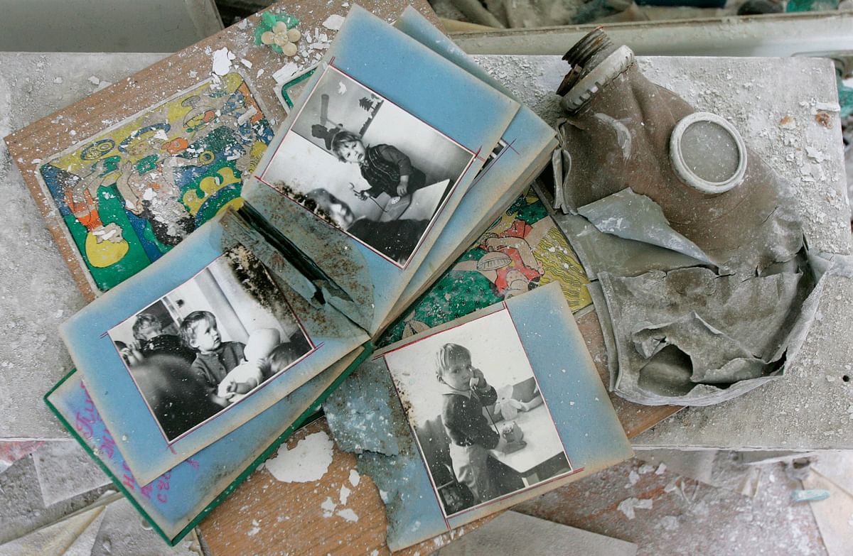 A family's photo album collects dust and debris, 30 years after the Chernobyl Nuclear Disaster. It lies next to an ominous gas mask, common in nuclear townships in USSR. (Photo: Reuters)
