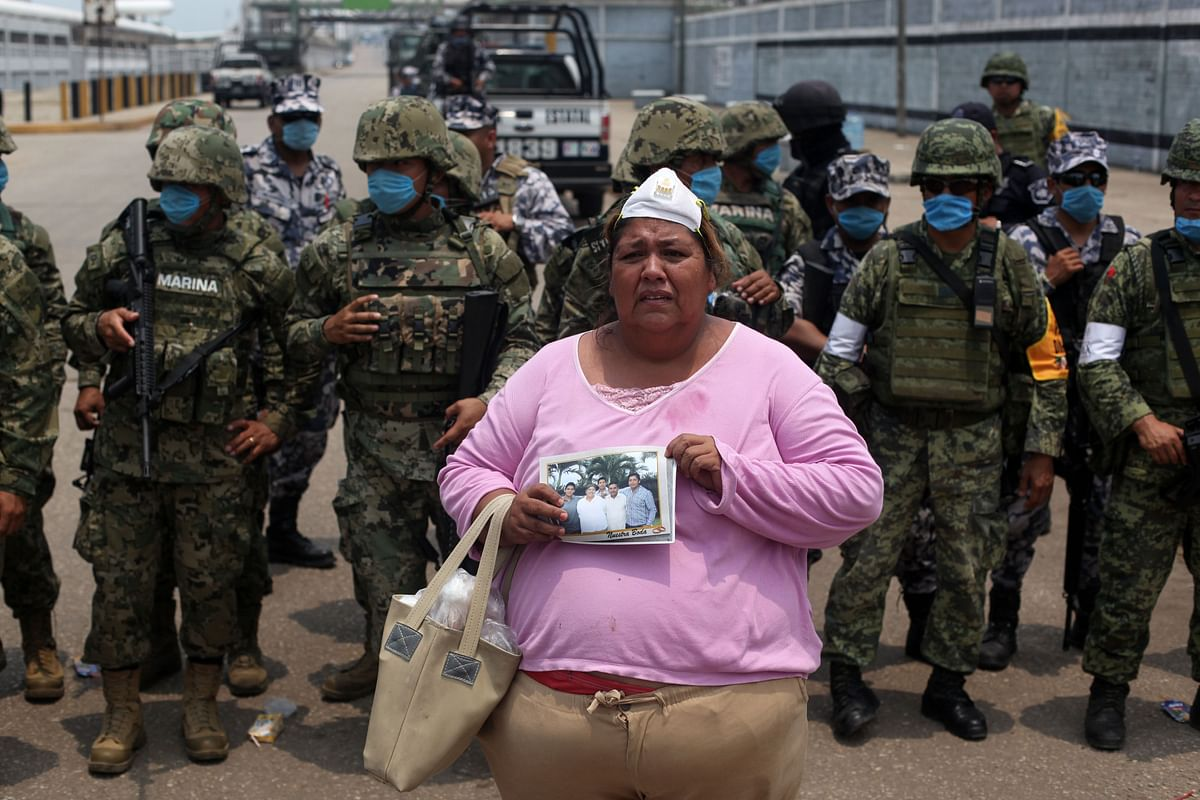Rosa Villalobos stands in front of army soldiers as she holds up a photo of her son, Luis Alfonso Ruiz, 25, (on the right of the photo), as she tries to get information on his whereabouts outside one of the main entrances to the Pajaritos petrochemical complex in the city of Coatzacoalcos, Mexico, Thursday, 21 April 2016. (Photo: AP)