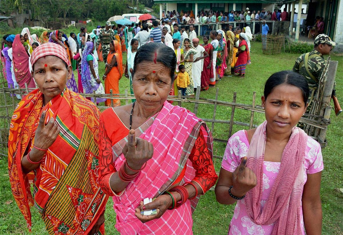 Tea tribe women showing their inked fingers after casting their vote during the first phase Assembly Elections for Duliajan Assembly Constituency at Bordubi. (Photo: PTI)