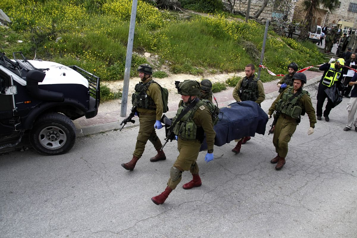 Israeli soldiers carry the body of one of the two Palestinians who was shot by an Israeli soldier. (Photo: AP)
