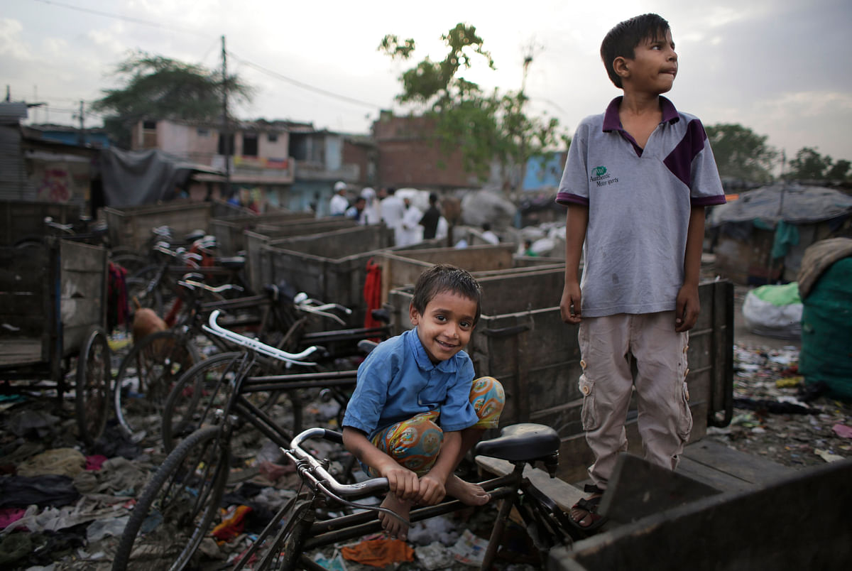 A young boy reacts to camera sitting on a cycle rickshaw as children play in the evening at a slum in New Delhi. The rickshaws are used by their parents to transport recyclable garbage.(Photo: AP Photo/Altaf Qadri)