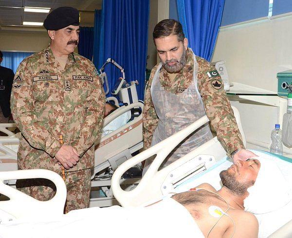 "Asim Bajwa with an injured soldier. (Photo: <a href=""https://twitter.com/AsimBajwaISPR/status/703841632219627520"">Twitter/@AsimBajwaISPR</a>)"