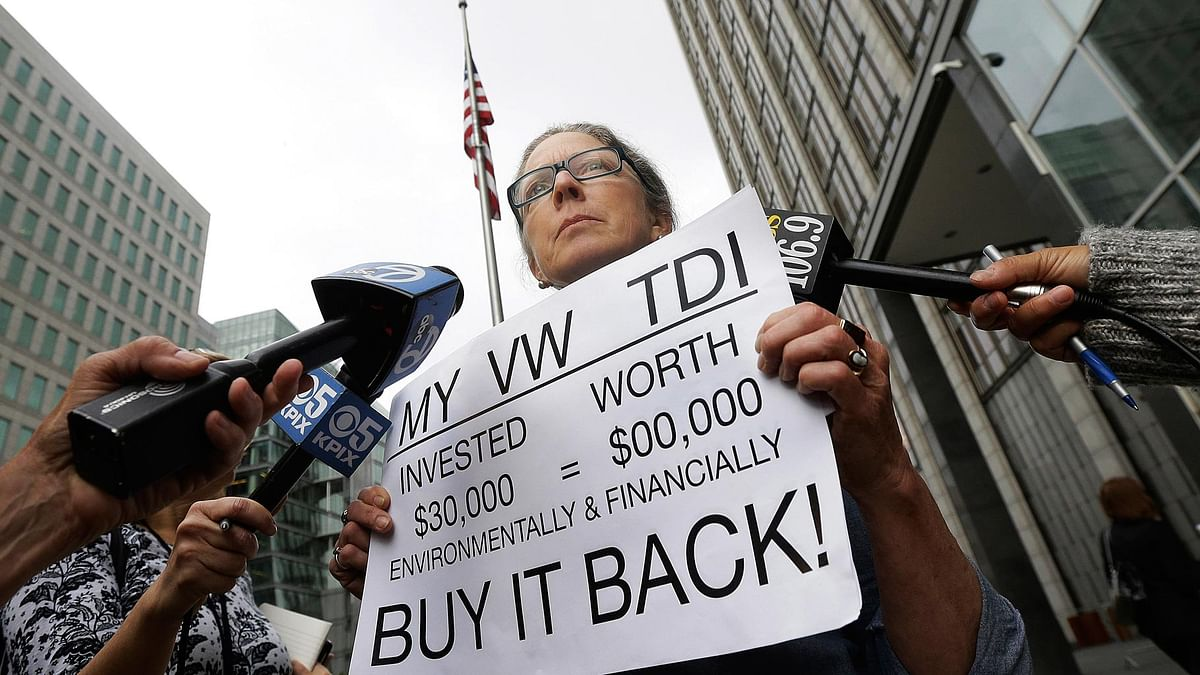 Joyce Ertel Hulbert, the owner of a 2015 Volkswagen Golf TDI, holds a sign while being interviewed outside of the Phillip Burton Federal Building in San Francisco, 21 April  2016. (Photo: AP)