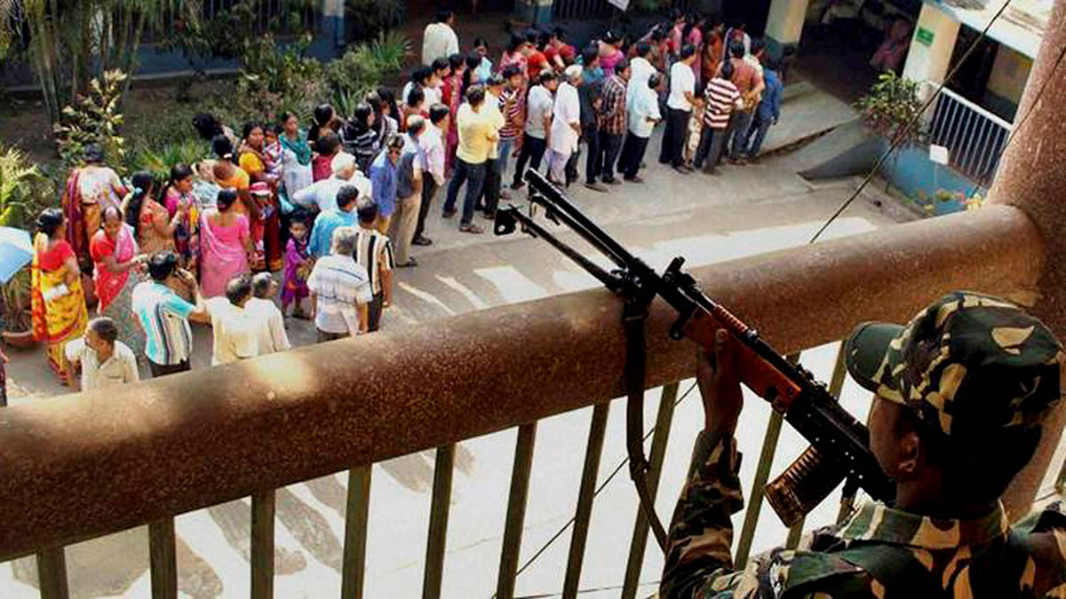 Security forces watch over voters lined up in front of a polling station. ( Photo : PTI )