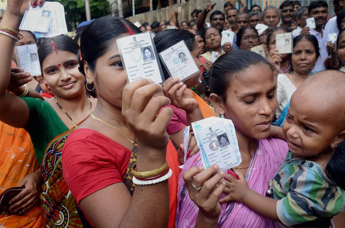 Voters show their voter cards at a polling station during 3rd phase of state assembly elections in Kolkata. (Photo: PTI)