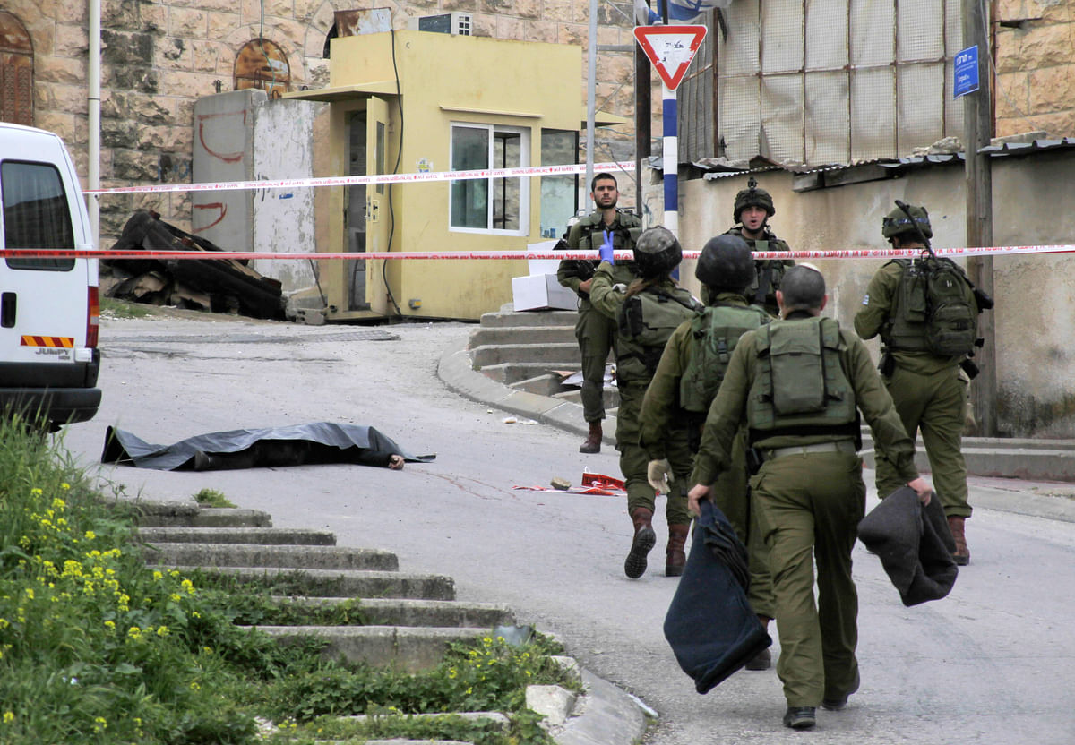 In this Thursday, 24 March  2016 file photo, Israeli soldiers stand near the body of a Palestinian who was shot and killed by a soldier while laying wounded on the ground after a stabbing attack in Hebron, West Bank. (Photo: AP)