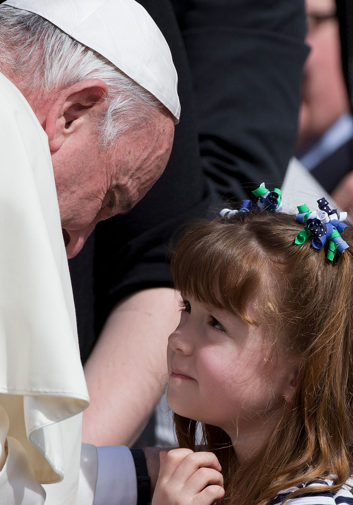 The Pope bent down so his head could reach the level of Lizzy's, softly touched the girl's eyes with his right hand and blessed her. (Photo: AP)