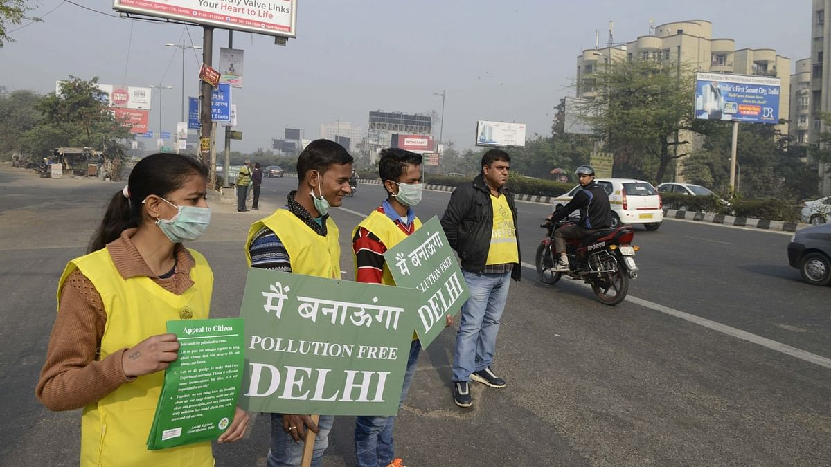 Volunteers stand on Delhi roads holding placards during Odd-Even Phase 2. (Photo: IANS)