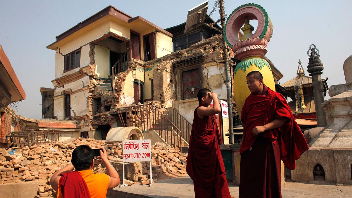 A monk takes photo of damaged monastery from last year's earthquake in the Swayambhunath stupa, in Kathmandu, Nepal, on 25 April, 2016. (Photo: AP)