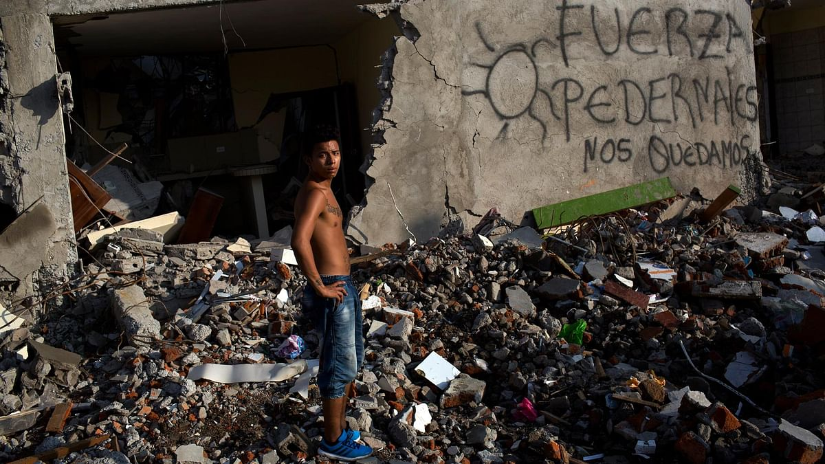 """A man stands in front of a destroyed building with graffiti on a wall that reads in Spanish """"Strength Pedernales, we will stay,"""" one week after the devastating earthquake, in Pedernales, Ecuador, Sunday, April 24, 2016.(Photo: AP)"""