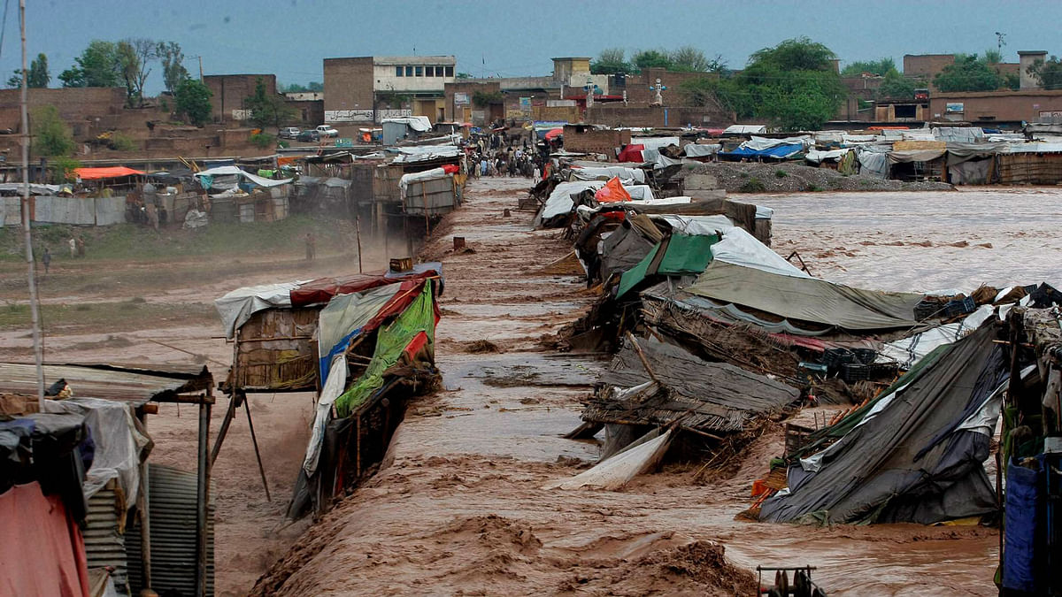 Pakistani villagers stand outside their homes during flash flooding.