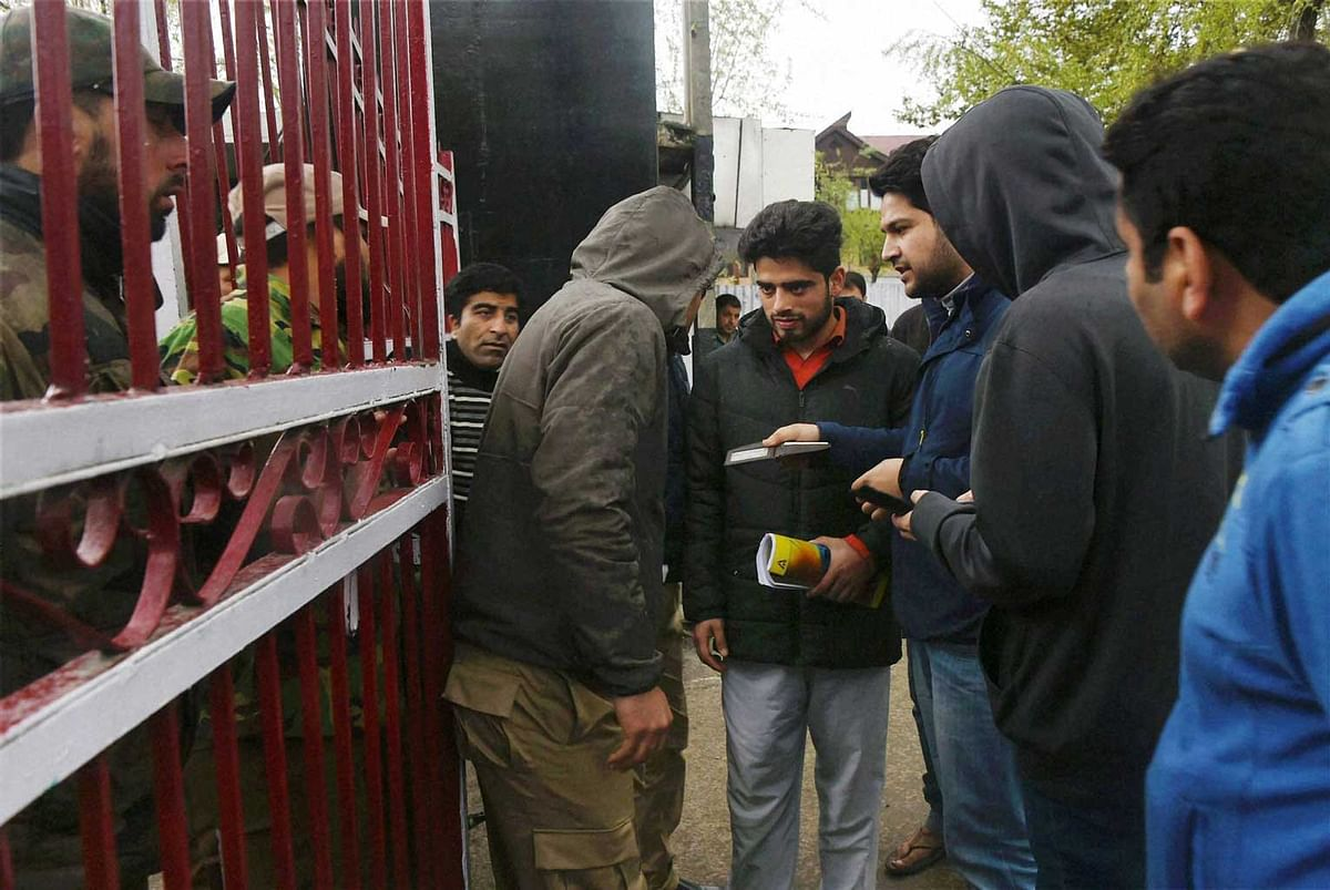 A police officer checks IDs of students at NIT following tension between the local and non-local students of the institute, in Srinagar on Wednesday, 6 April 2016. (Photo: PTI)