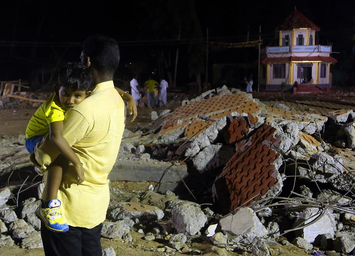 A man holds his child at the site of blast in Paravoor village, Kollam district, southern Kerala state, India, Sunday, 10 April 2016. (Photo: AP)